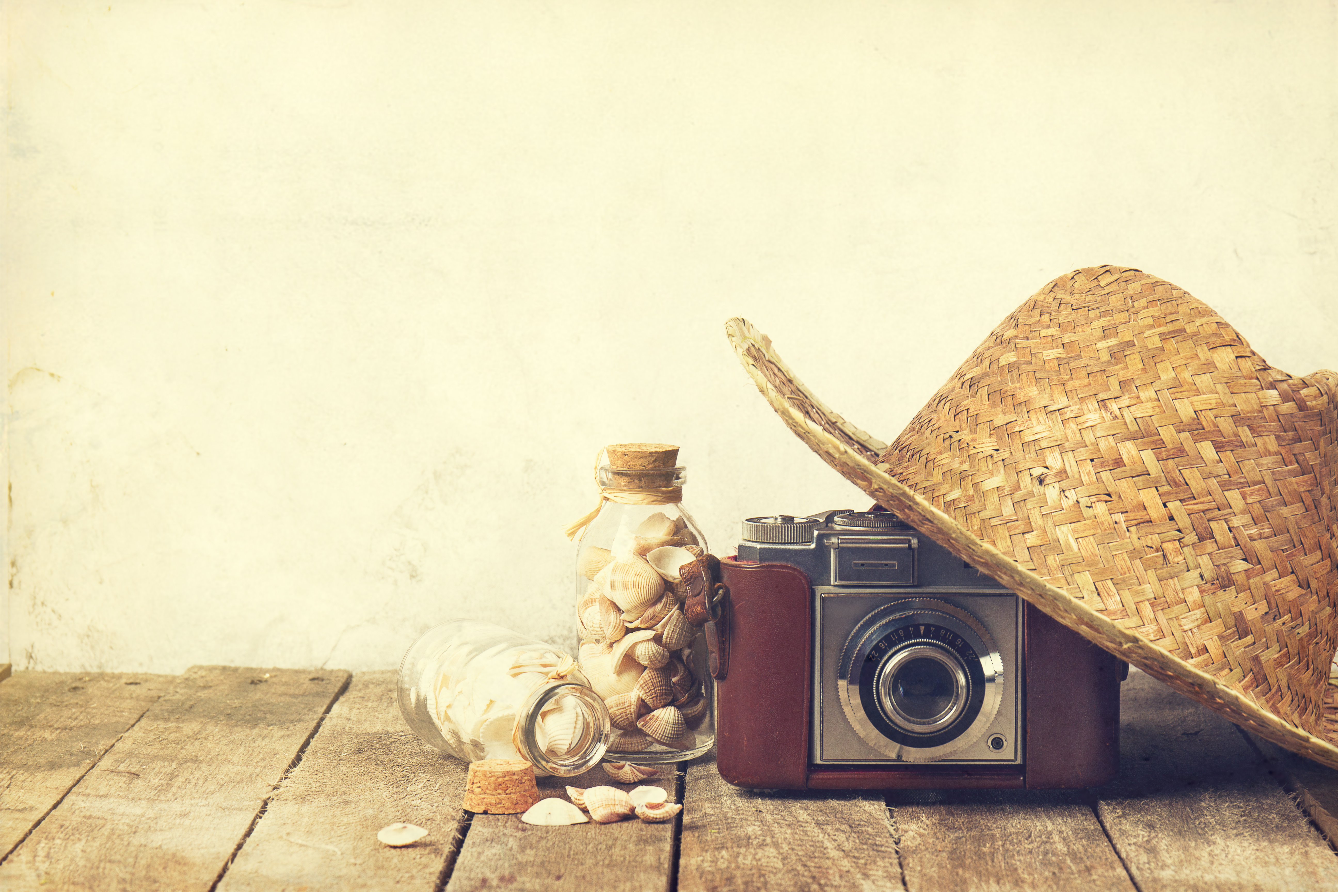 Summer or vacation concept. Straw hat with old vintage camera and shells on wooden background.