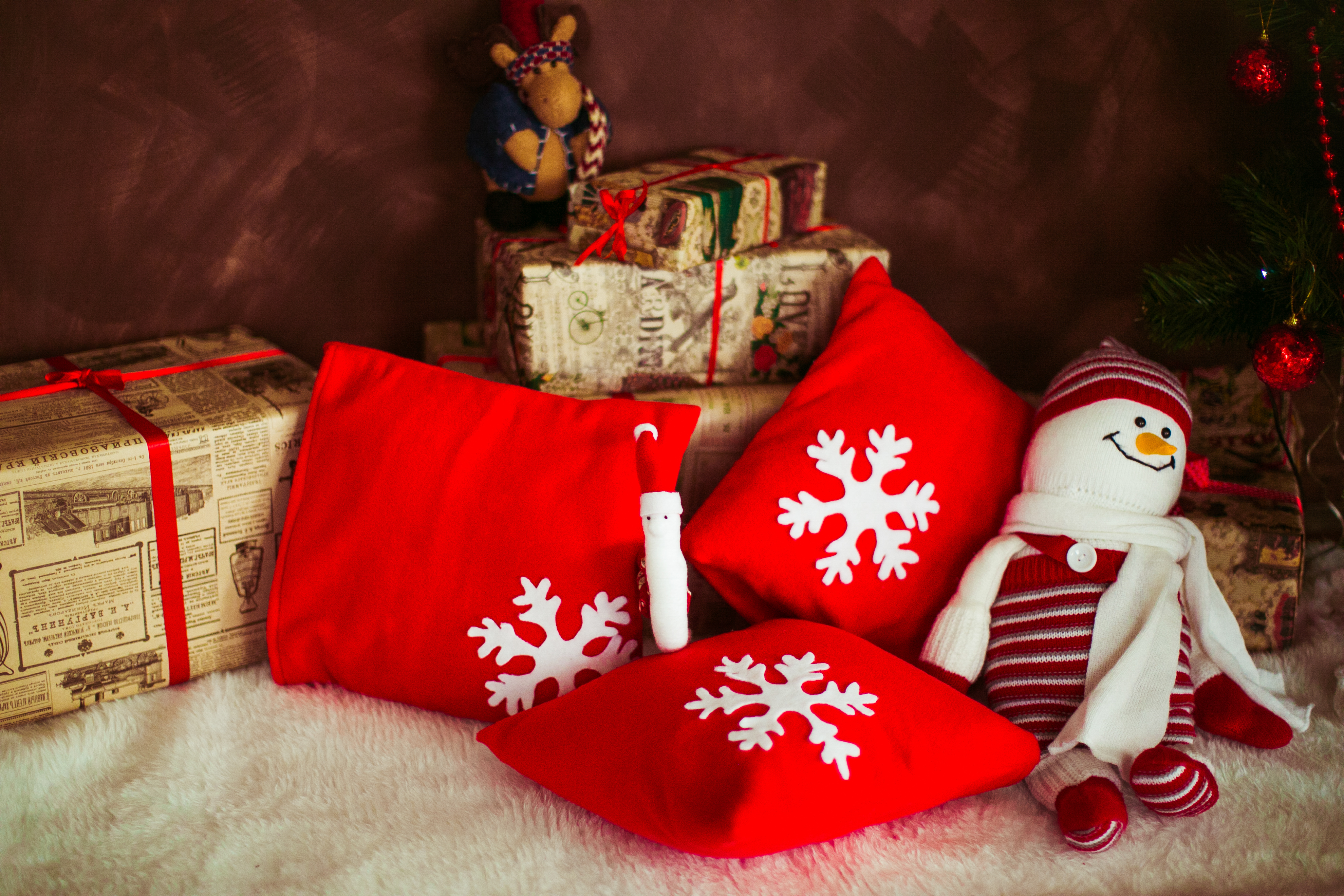 Red pillows with snowflakes and toy snowman lie on the floor